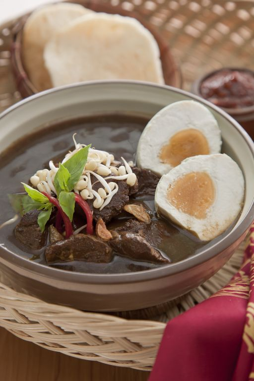 Rawon Komplit. A hearty black beef soup cooked with black nut served with salted egg.