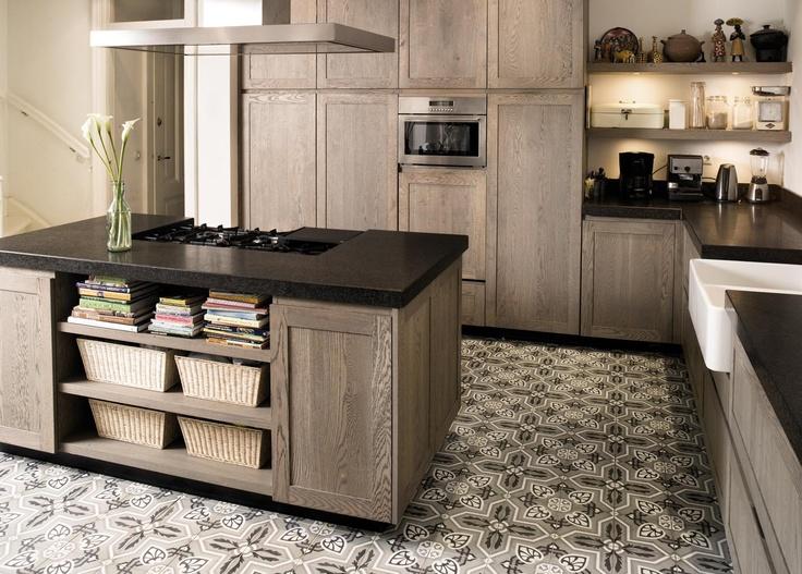 Op maat gemaakte houten keuken. Deze prachtige op maat gemaakte keuken van Fred Constant biedt volop werkplek. Doordat er in het keukenblad een uitsparing voor de spoelbak is gemaakt, kan deze lager geplaatst worden. Dit is vaak handiger in het gebruik. Voor de vloer is gekozen voor handgemaakte Portugese tegels. Door te kiezen voor een doorlopend patroon wordt het geheel niet te druk.