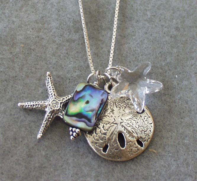 Sea Life Charm Necklace by dandelion jewelry & accessories Sterling silver sand dollar and starfish charms dangle together with a swarovski crystal starfish and abalone accent on a 30″ box style chain. $75