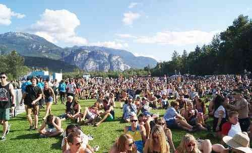 Crowds on the grass in Squamish, with a view of the Stawamus Chief mountain in the background