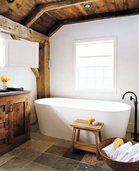 Master bathroom with modern stand alone tub, stone floors, exposed beams and reclaimed wood cabinets and drawers