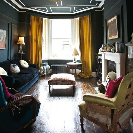 Jo Kornstein living room: Farrow & Ball Black Blue walls, brown stained wood floors and brown velvet armchair with yellow curtains