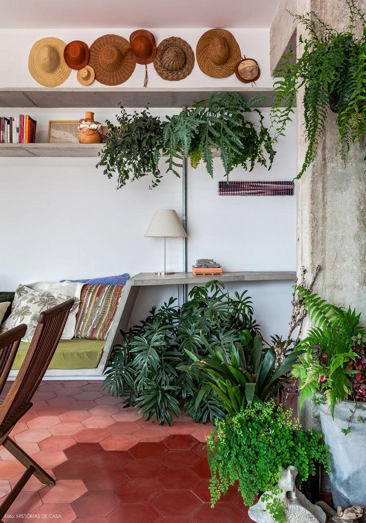 Concreto, ladrilhos hidráulicos em tons de rosa e muitas plantas nessa sala de estar. Para arrematar a decoração, composição de chapéus na parede.