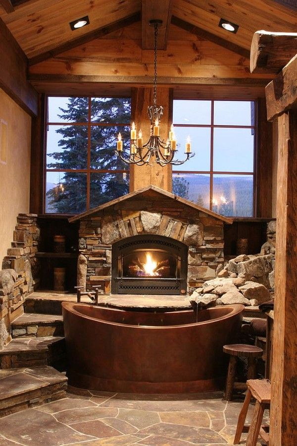 Fabulous cabin-style bathroom with copper bathtub, fireplace and large windows