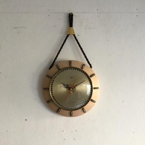 SMITHS(スミス)の壁掛け時計|SMITHS(スミス)社のウォールクロックです!ゴールドのフレームとファブリックのロープで吊り下げる素敵な壁掛け時計。文字盤の細かいところまでデザインされた70年代らしいモダンでアンティークが上手にミックスされたモチーフですね!スミス社は1851年に時計職人のサミュエル・スミスが開いた時計店が始まり。 時計メーカーとしての地位を確立、航空機の速度計、気圧計をはじめ、ミニなど英国車のスピードメーターにも使われていたクールな時計メーカーです。