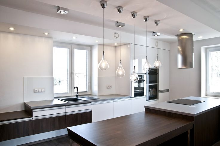 Velice moderní kuchyňská sestava působící luxusním dojmem. Majitelé vsadili na bílou lesklou barvu a velmi oblíbený dekor ořechu Ribera.