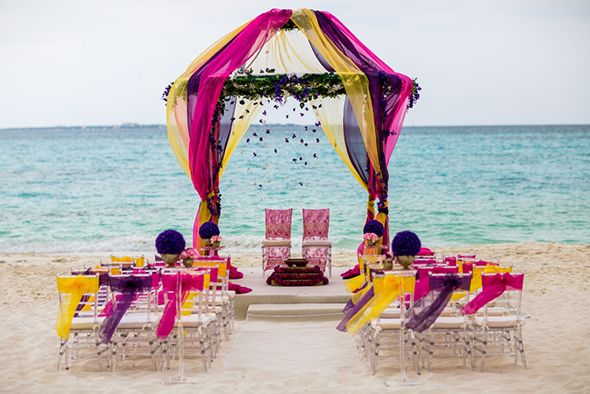 Colorful wedding arch ideas for tropical destination wedding in Cancun, Mexico at Grand Fiesta Coral Beach Resort. || Seen on: http://www.jetfeteblog.com/wedding-locations/luxury-resort-destination-weddings-cancun