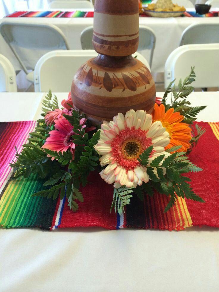 Centro de mesa típico mexicano con flores y un botellón artesanía mexicana