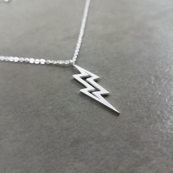 Lightning is a sudden electrostatic discharge that occurs during a thunder storm. This discharge occurs between electrically charged regions of a cloud, between two clouds, or between a cloud and the ground.  Pendant:    Silver plated  1 inch x 1/4 inch(24 mm x 6 mm)    Chain Size:    Silver plated  1 mm in width  17.5 inches in length