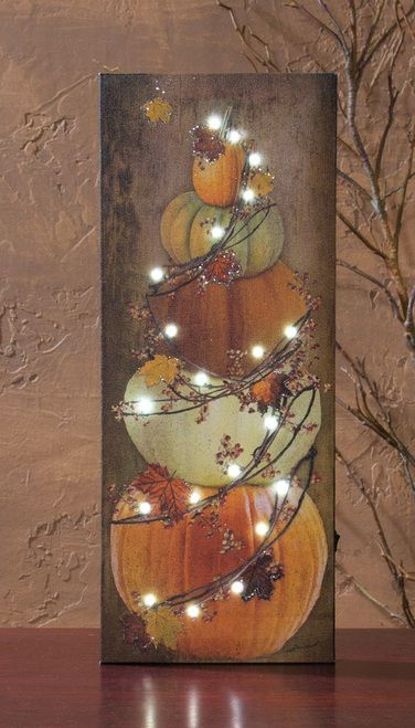 lighted country art print of a stack of pumpkins with a vine and lighted garland.  Battery power LED lights and a timer feature power this lighted art by Radiance Lighted Canvas