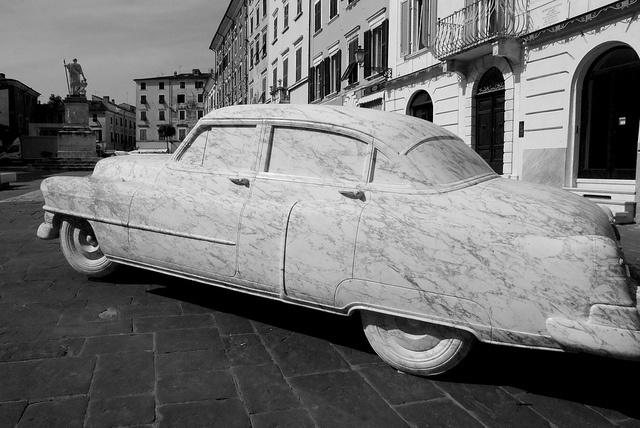 """La Cadillac, tirata a lucido nella """"Scuola di Torano"""" collocata in Piazza Alberica, valorizzata con un'illuminazione studiata appositamente;  è una scultura imponente, lunga 545 centimetri, alta 165 e larga oltre due metri, pesa circa quattordici tonnellate; è stata realizzata da un unico blocco di arabescato che, in origine, pesava 70 tonnellate, estratto nella cava """"Cardellino"""" che si trova nel bacino di Colonnata."""
