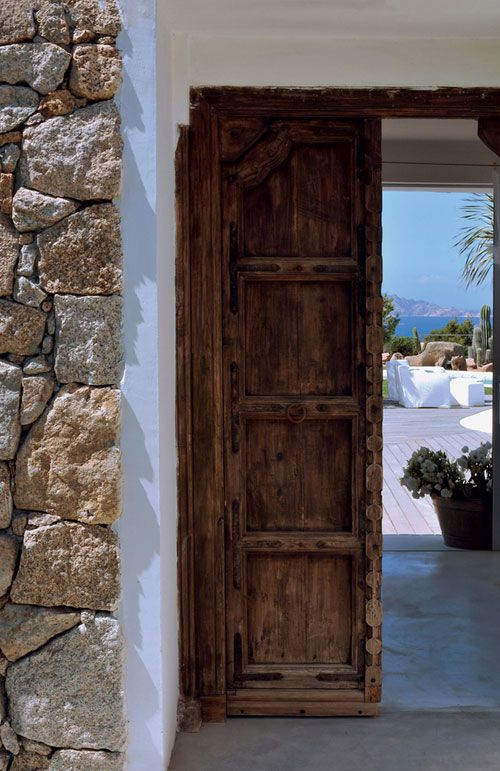 Sardinia, Italy. The interior is designed by Marina Wenger from Geneva. Most furniture pieces and accessories come from Asia: doors from Indian and other Indian and Chinese pieces create a warm and rustic look throughout the house.