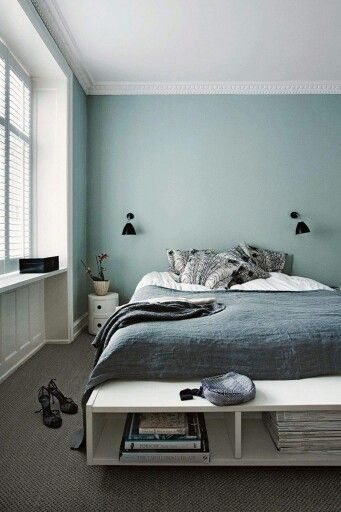 pale blue wall with gray bedding
