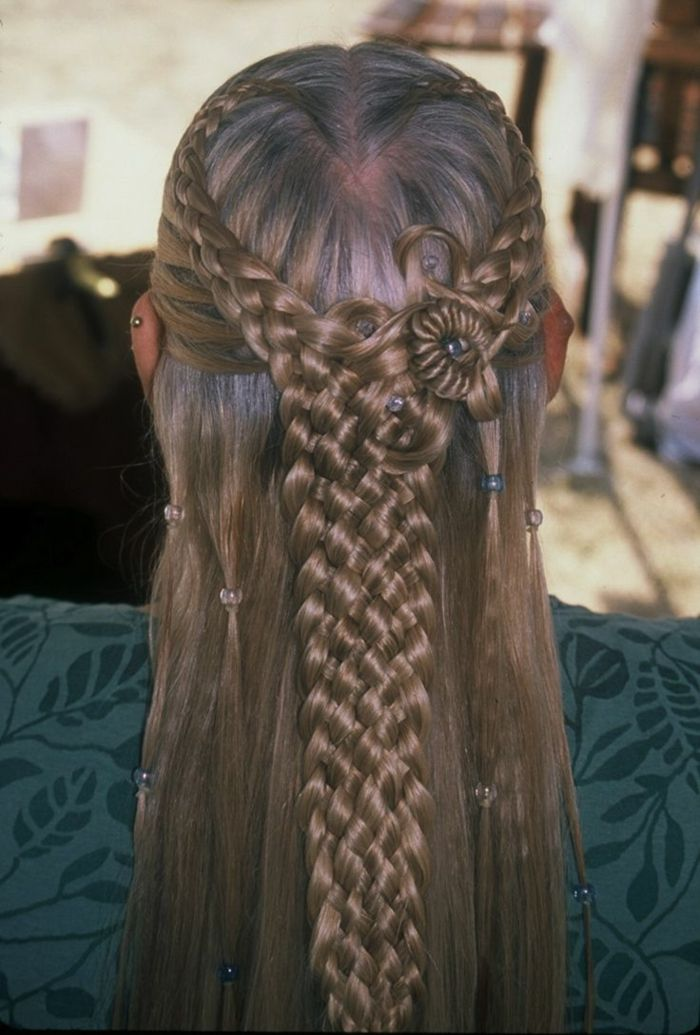 medieval hairstyles, dark brown hair, partially woven in several braids from each side, joining together in the middle, to form one thick braid, clear and green beads in hair, green top with leaf pattern