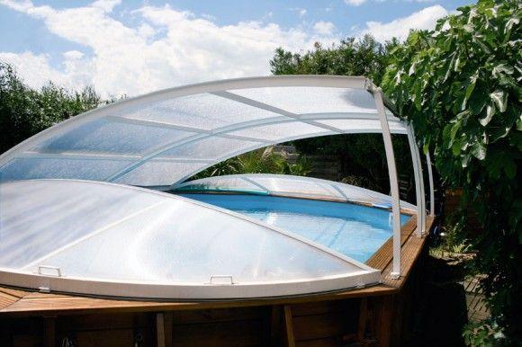 Un abri bas relevable fixé sur les margelles d'une piscine hors sol