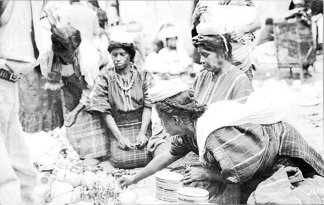 Guatemalan Maya Women | by Teyacapan. old postcard. they are from San Juan Sacatepéquez, Guatemala, near the capital, Guatemala CIty. They are Cakchiquel Maya. The traje has not changed that much, but not many women still wear wool in their braids. Huipil is purple, yellow & red, sometimes also green, with very bold brocaded animals. Corte is black with white criss cross lines and handsome handmade randa (embroidery that holds the 2 sections together). The woman standing to the left is ....