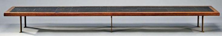 Pierre LEBE (1929-2008) Longue table basse, le plateau en placage d'ardoise dans un entourage de chêne, elle pose sur six pieds plats en bronze doré s'évasant légèrement pour former un L à la réception… - De Baecque et Associés - 11/02/2017