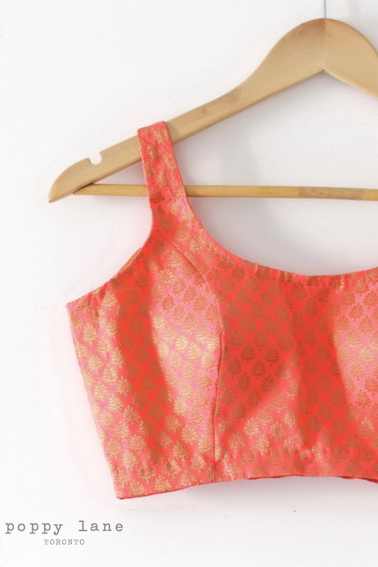 Sunrise -  Sleeveless bright coral and gold chanderi blouse with open back. Includes padded chest. Zipper enclosure on side. Shop now at poppylane.ca