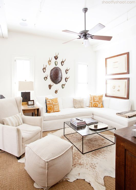 Chic country living room features tortoise shell surrounded by small mounted antlers over white sectional sofa accented with tan and orange pillows and Hermes Avalon Throw flanked by farmhouse end tables topped with black and gold lamp paired with off-white wingback chair with matching cube ottoman and industrial coffee table over cowhide rug layered over sisal carpeting.
