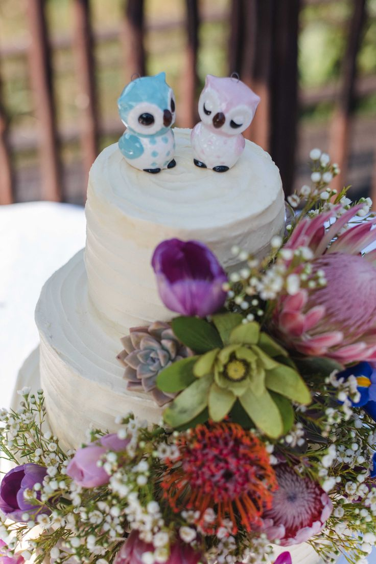 Our wedding cake. Owl cake toppers. Protea, tulip, iris and babies breath