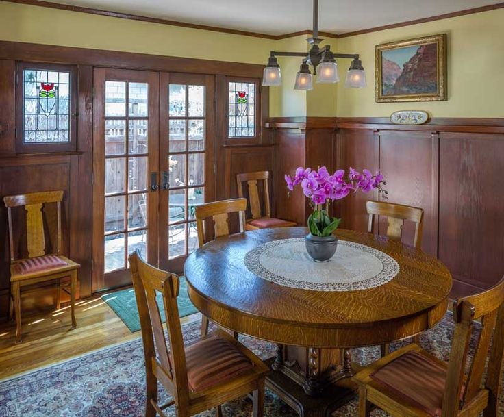 In the dining room, French doors replaced a plate-glass window flanked by small casements. The tiger-oak table is ca. 1895; chairs are vintage, as are textiles with Arts & Crafts embroidery.
