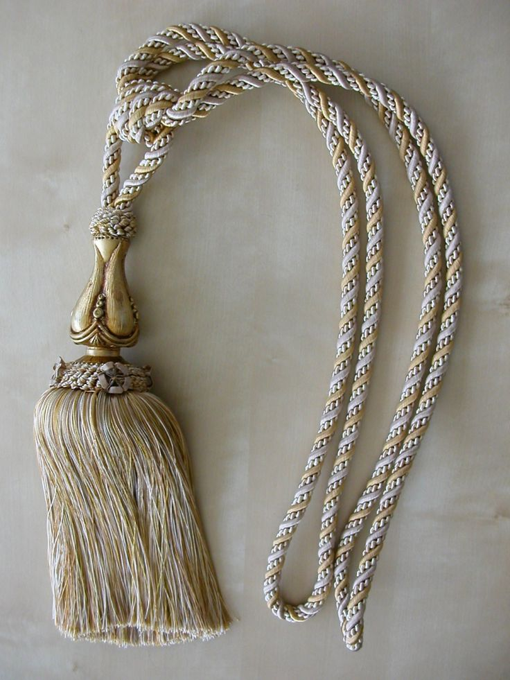 Klasszikus zsinóros függönyelkötő bojt, arany kevert színben. Színminta alapján 20 színből rendelhető. Kikötő teljes hossza 82 cm, bojt hossza fa díszítéssel 29 cm