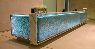 A textured caste glass reception desk with a marble racetrack counter top constructed by Benchmark Furniture with glass by specialists Fusion glass