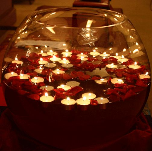 A beautiful, yet inexpensive centerpiece! A fish bowl, flower petals, and floating tea candles. How gorgeous!