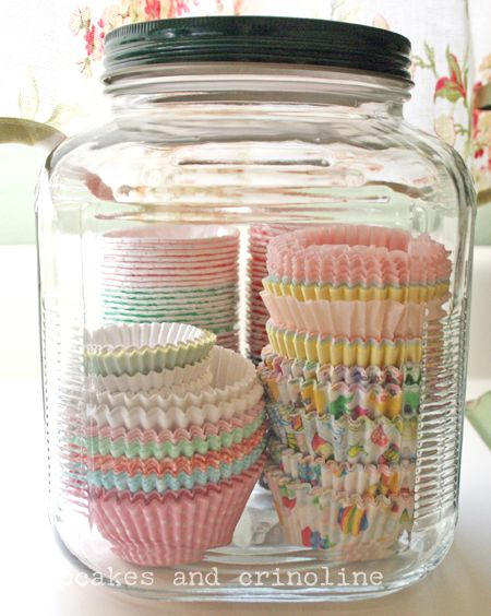 Use large jars in your kitchen to unclutter, organize and create pretty vignettes with small kitchen items including cupcake wrappers, cookie cutters and more. Kitchen Storage in Glass Jars - baking supplies at cupcakesandcrinoline.com
