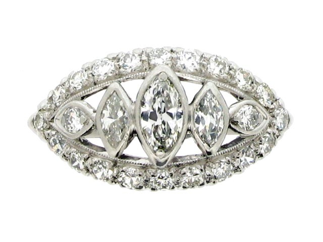 Old cut marquise and round diamond ring, American, circa 1950. A platinum and iridium ring horizontally set with three marquise shaped old cut diamonds graduated from centre and in collet settings with an approximate total weight of 0.40 carats, flanked by two round old cut diamonds in grain settings, all in a pierced millegrained surround, bordered by a single row of twenty round old cut diamonds in claw settings, all twenty two round diamonds with an approximate total weight of 0.66…