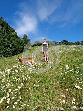 Teen girl with dog walking among chamomile field, green trees around, blue sky