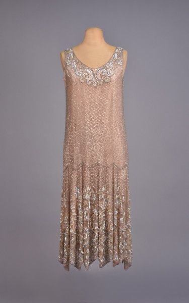 BEADED and SEQUINED SILK DRESS, 1920s Sleeveless pink tulle with an allover tiny diamond lattice of bugle beads, the neckline and lower skirt decorated with a stylized floral in opalescent sequins and tiny gold beads, handkerchief pointed hem, pink silk underdress. - whitakerauction