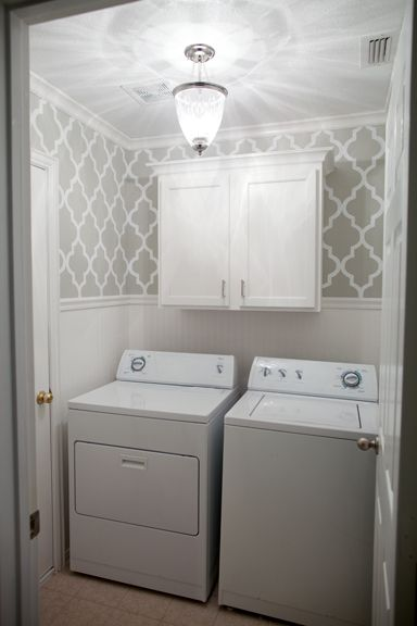 grey stenciled laundry room with wallpaper wainscoting