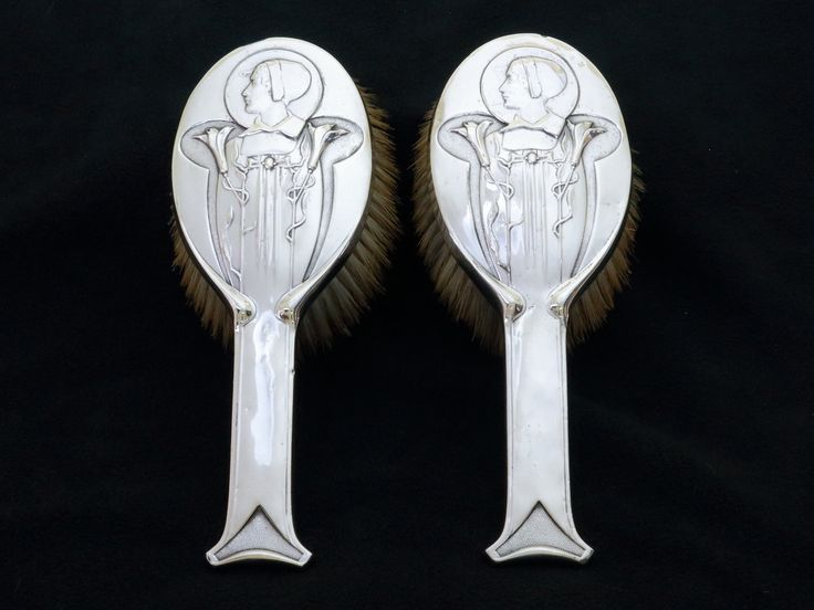A pair of Art Nouveau silver mounted hair brushes designed by Kate Harris for William Hutton and sons.  Hallmarked London 1904 with William Hutton & sons makers mark, along with registered design number.