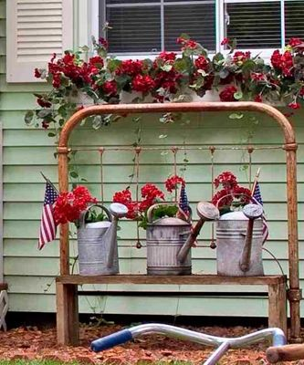 An old iron bed frame makes a wonderful garden accent. At their Shelby Township, Michigan, home, Karen and Bob Grinn put a bench in front of the headboard and lined up metal watering cans for an eye-catching display. Photographed and styled by Franklin and Esther Schmidt.