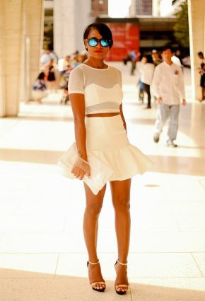 White cropped top paired with matching flared mini skirt and clutch.