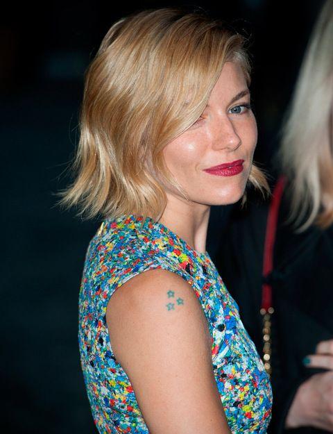 La actriz Sienna Miller luce tres pequeñas estrellas de color azul en el hombro derecho. Además de éste, tiene otros dos pequeños tatuajes: un pájaro en la muñeca y otra estrella en el estómago.