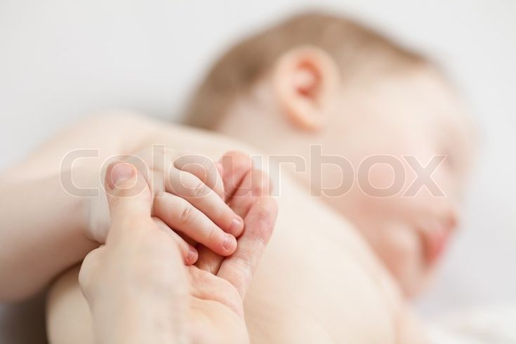 Stock image of 'Parent's hand holding baby's hand'
