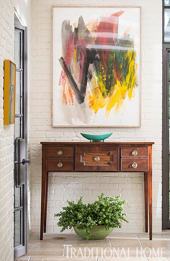 A 19th-century mahogany sideboard pairs with artwork by Elyssa Rundle through John Pope Antiques. - Traditional Home ® / Photo: John Bessler / Design: Lisa Hilderbrand with Sarah Hamlin Hastings