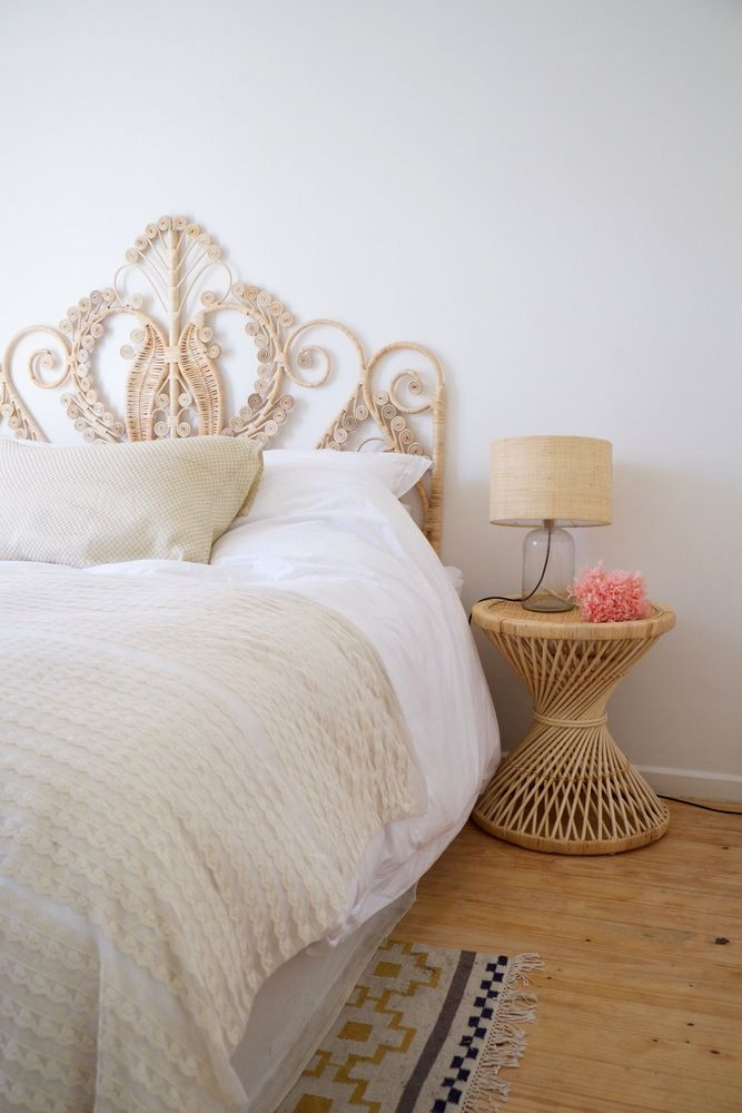 A natural + white bedroom with peacock headboard and rattan side table