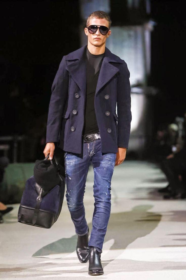 Dsquared2 fall winter 2015. Abrigo azul marino, camiseta negra, jeans ultra fit, bolso de viaje y botas negras.