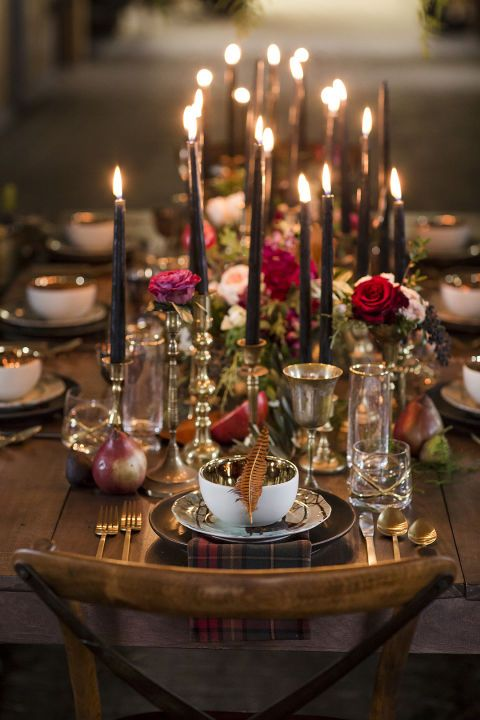 A single feather and a plaid napkin for each place setting, paired with moody black candles, makes this wedding tablescape indisputably autumnal.
