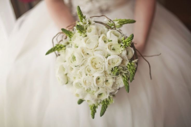 A rounded, hand-tied bouquet of white ranunculus with a twisted curly willow wreath and star of Bethlehem border.