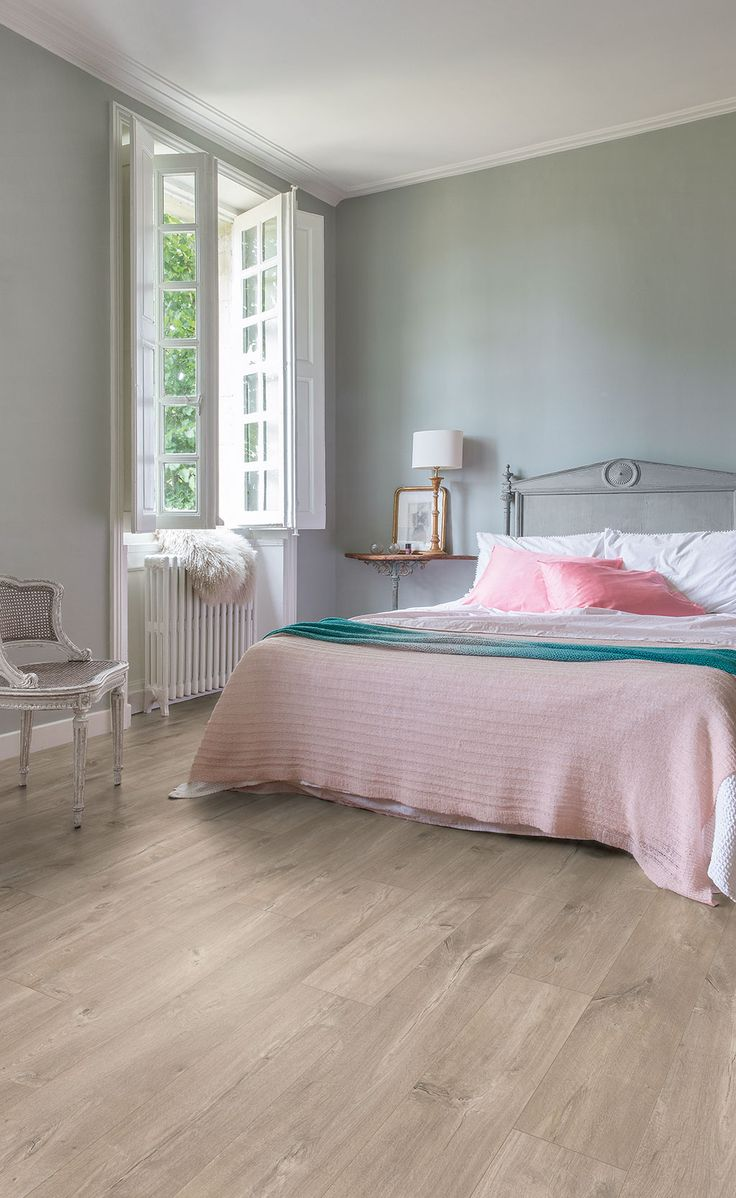 Quick-Step Laminate Flooring -  Perspective Wide 'Carribean oak grey' (UFW1536) in a classic bedroom. To find more bedroom inspiration, visit our website: https://www.quick-step.co.uk/en-gb/room-types/choose-the-perfect-bedroom-flooring #chambre #slaapkamer