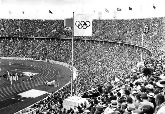 The Olympic Flag and the Nazi Flag fly side by side in Olympic Stadium, 1936.