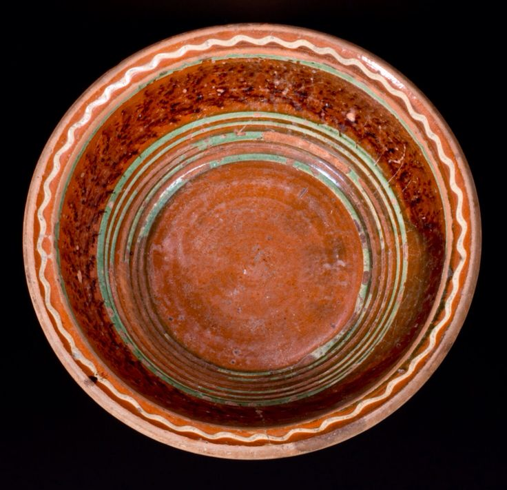 Crocker Farm 3/19/16 Lot # 423.  Realized: $144 ($125 hammer, plus 15% buyer's premium).  Glazed Redware Bowl with Three-Color Slip Decoration, Mid-Atlantic origin, second or third quarter 19th century, tapered bowl with semi-rounded rim, the interior decorated with several bands of copper slip below a wide band of manganese sponging. Rim area decorated with a wavy band of cream-colored slip above a band of copper slip. Wear to interior, including heavy losses to copper slip below rim and…