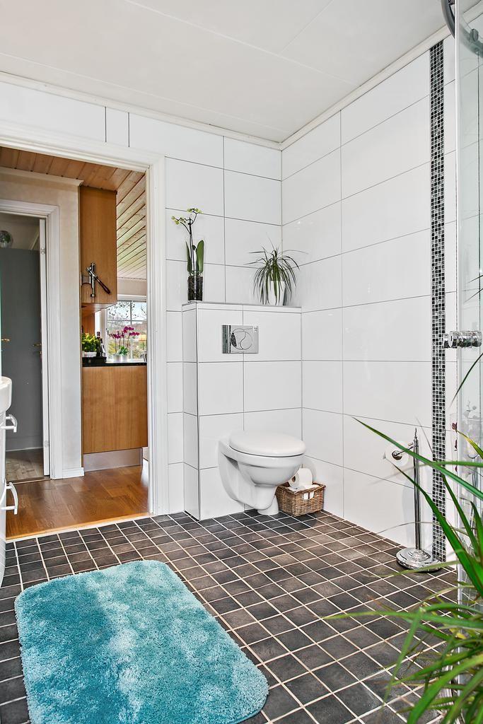 Helkaklat med detaljer av glasmosaik. Vägghängd toalett gör badrummet stilrent.