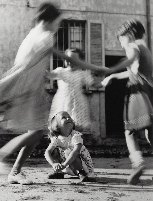 black & white photo, 3 little girls holding hands, laughing as they circle around a 4th little girl who is squatting, happy, dance, children Vitaliano Bassetti