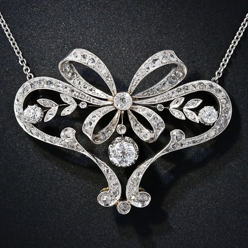 From the turn-of-the-twentieth century comes this truly exquisite Edwardian necklace, elegantly fashioned in a flowing multi-dimensional ribbon motif and wrapped with a sparkling platinum and diamond bow. A quarter-carat old mine-cut diamond, set in a buttercup setting, swings in the center. Magnificently rendered in platinum over rich 18 karat yellow gold. 1 and 5/8 inches wide by 1 and 1/4 inch high; the newer platinum chain measures 15 inches.
