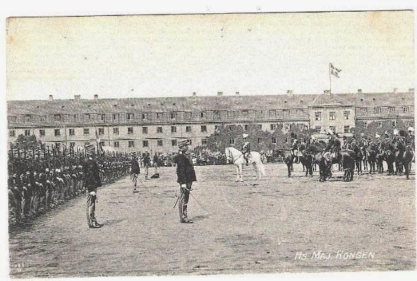 King Christian X on horse wearing the uniform of the Danish Royal Guards with bearskin shacko inspecting troops at the Rosenborg Military Base
